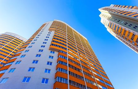 stock-photo-tall-apartment-buildings-on-blue-sky-background-188116835-448x288.jpg